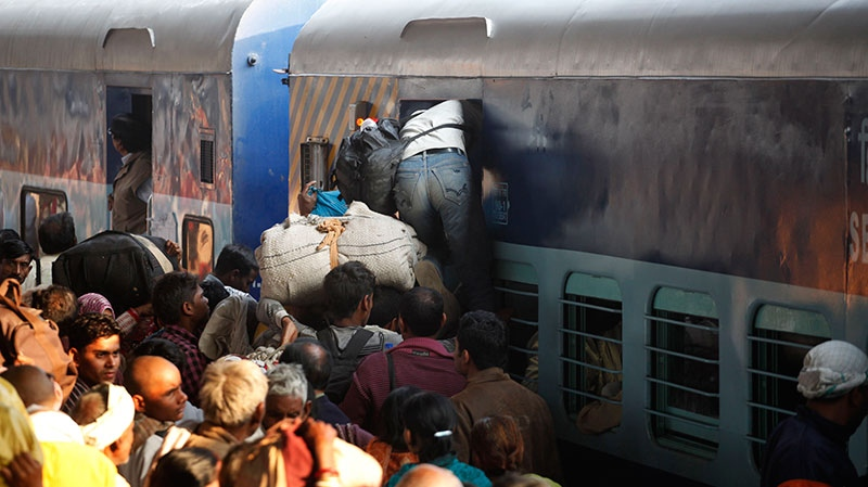 Hindu devotees returning from Maha Kumbh jostle to get in a coach of a train at the main railway station of Allahabad, India, Monday, Feb. 11, 2013. (AP / Rajesh Kumar Singh)
