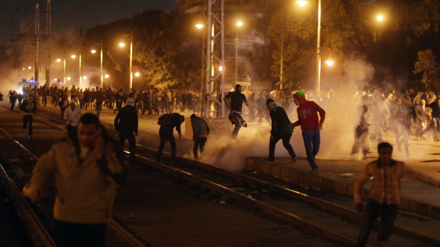 Egyptian protesters run from tear gas