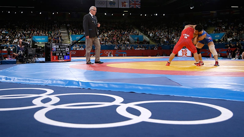Cuba's Gustavo Balart, left, competing with South Korea's Choi Gyu-jin during 55-kg Greco-Roman wrestling competition at the 2012 Summer Olympics in London, Aug. 5, 2012. (AP / Paul Sancya)