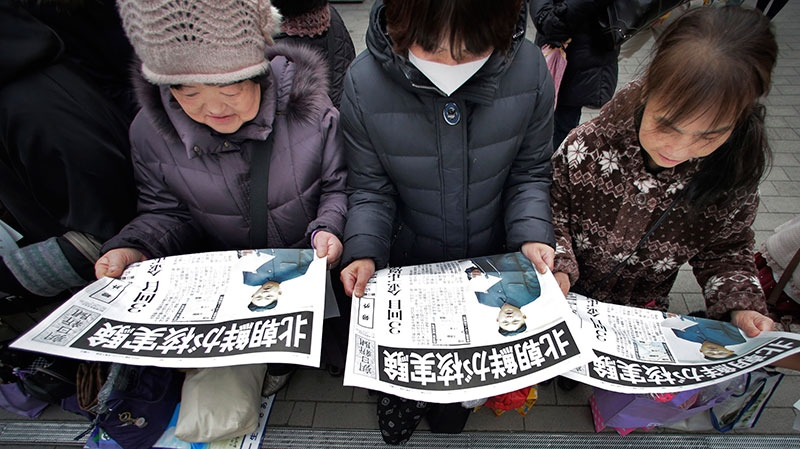 Women read copies of a delivered extra edition of a Japanese newspaper reporting North Korea's nuclear test, in Tokyo Tuesday, Feb. 12, 2013. (AP / Itsuo Inouye)
