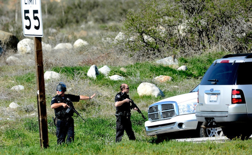 Heavily-armed police officers man a blockade near the entrance to the San Bernardino National Forest in southern California after Christopher Dorner, a fugitive ex-Los Angeles cop sought in three killings, engaged in a shootout with authorities that wounded two officers in the San Bernardino Mountains near Big Bear Lake, Tuesday, Feb. 12, 2013. (The Sun / Gabriel Luis Acosta)