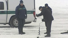 Workers measure the thickness of the ice at Dow's Lake, Wednesday, Jan. 12, 2011.