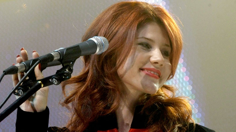 Anna Chapman, who was deported from US on charges of espionage, on stage with the leaders of Young Guards, a pro-Kremlin youth movement she joined, in Moscow, Russia, Wednesday, Dec. 22, 2010. (AP / Mikhail Metzel)