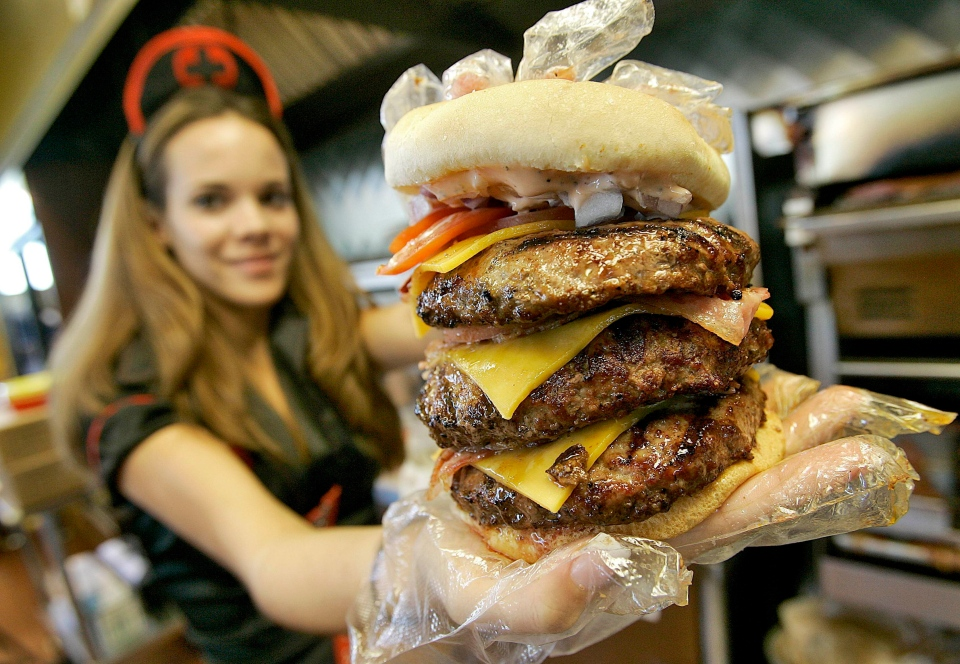 Courtney Chapman, a waitress dressed as a nurse at the Heart Attack Grill in Arizona, holds up a triple bypass burger.  (AP Photo/Matt York)