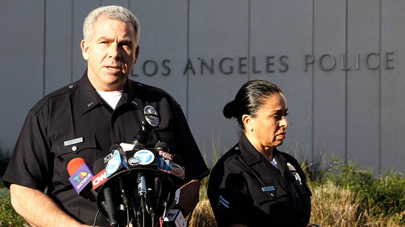 LAPD spokesman Lt. Andy Neiman, left, with officer Norma Eisenman, talks to reporters during a news briefing at LAPD headquarters regarding Christopher Dorner, Wednesday, Feb. 13,2013. (AP / Richard Vogel)