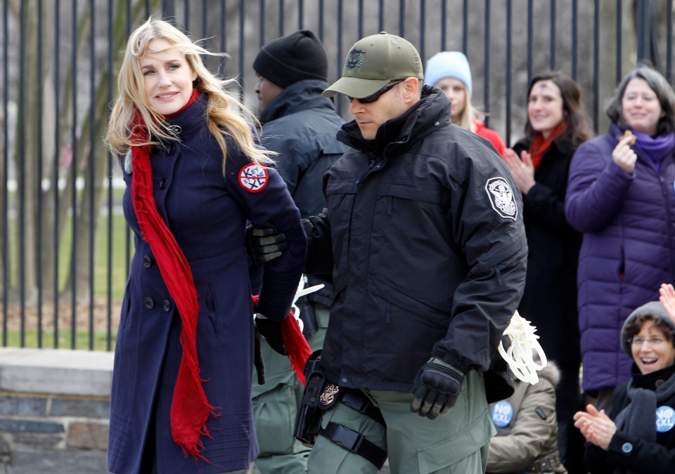 Actress Daryl Hannah is arrested outside the White House in Washington on Feb. 13, 2013, as prominent environmental leaders tied themselves to the White House gate to protest the Keystone XL oil pipeline. (AP Photo/Ann Heisenfelt)