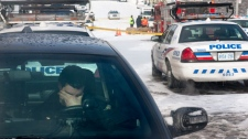 A Toronto police officer sits in his car near the site where Police Sgt. Ryan Russell was struck by a stolen snowplow in Toronto on Wednesday January 12, 2011. (Chris Young / THE CANADIAN PRESS)