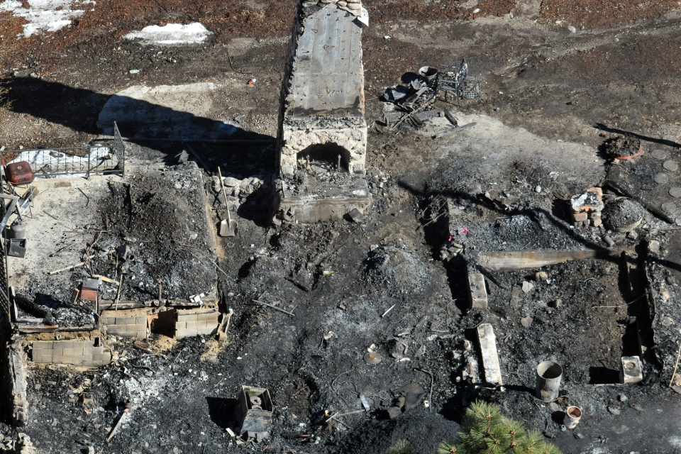 In this aerial photo, law enforcement authorities investigate the charred remnants of a cabin in the Angeles Oaks area of Big Bear, Calif., Wednesday, Feb. 13, 2013. (The Sun / John Valenzuela)