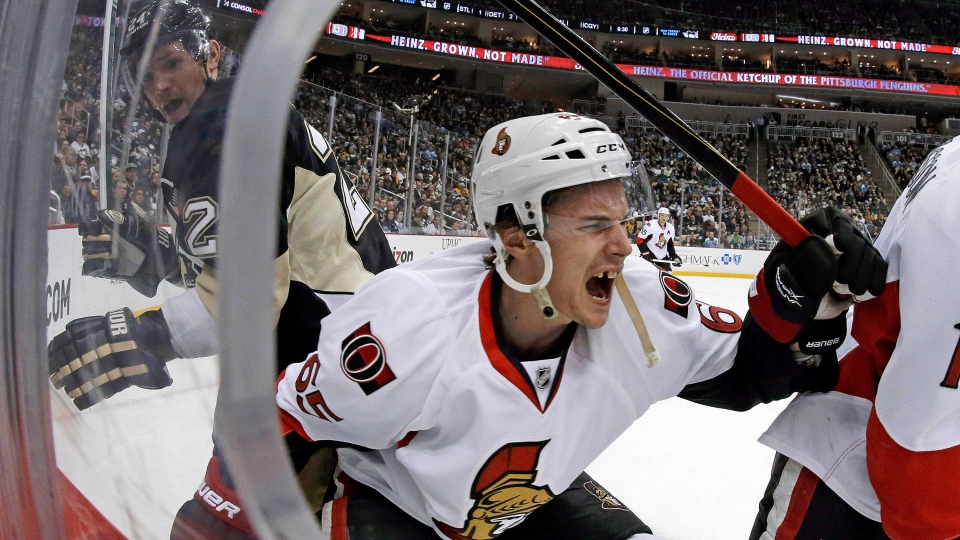 Ottawa Senators defenseman Erik Karlsson (65) grimaces as he falls to the ice after colliding with Pittsburgh Penguins left wing Matt Cooke, left, during the second period of an NHL hockey game in Pittsburgh on Wednesday, Feb. 13, 2013. (AP Photo/Gene J. Puskar)