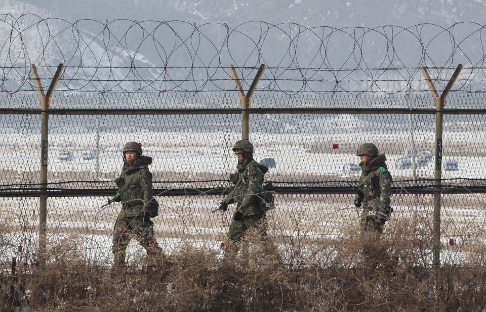South Korean army soldiers patrol along the barbed-wire fence under a heightened alert put in place in the wake of North Korea's nuclear test near the demilitarized zone of Panmunjom, in Paju, South Korea, Thursday, Feb. 14, 2013. (AP / Ahn Young-joon)