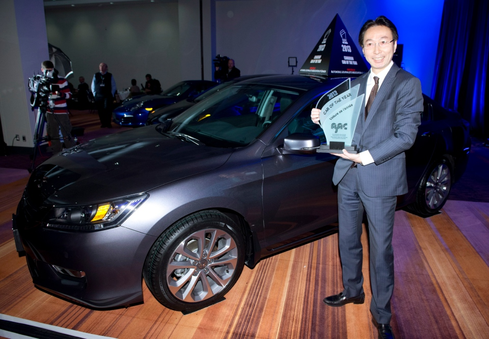 Takashi Sekiguchi, President and CEO, Honda Canada Inc., holds The Automotive Journalists Association of Canada award for the 2013 Canadian car of the year which was awarded to the Honda Accord Sedan at the Canadian International Auto Show in Toronto on Thursday, Feb. 14, 2013. THE CANADIAN PRESS/Frank Gunn