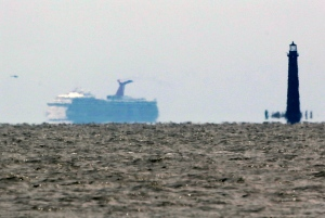 The cruise ship Carnival Triumph is visible several miles beyond the Sand Island Light House near Dauphin Island, Ala., Thursday, Feb. 14, 2013. (AP / Dave Martin)
