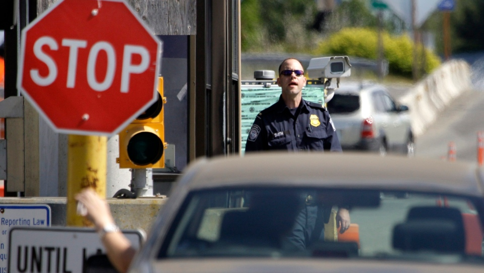 A U.S. Customs and Border Protection officer looks toward a car coming toward him in this 2009 file photo. (AP / Elaine Thompson)