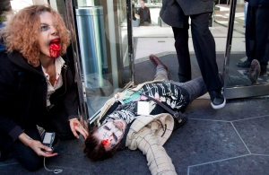 A member of the Occupy Vancouver movement lays on on the ground at the front doors of the Embridge offices during a Zombie Walk through downtown Vancouver, B.C. Monday, Oct. 31, 2011. (Jonathan Hayward / THE CANADIAN PRESS)