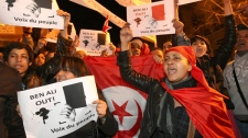 "Demonstrators shout slogans to call for the resignation of Tunisian President Zine El Abidine Ben Ali, during a demonstration in Marseille, southern France , Wednesday, Jan. 12, 2011. Tunisia's prime minister said Wednesday the country's interior minister has been fired after deadly protests over unemployment and also announced that most prisoners arrested during nearly a month of riots are being freed. Placards read : "" Ben Ali out, voice of the people"". (AP Photo/Claude Paris)"