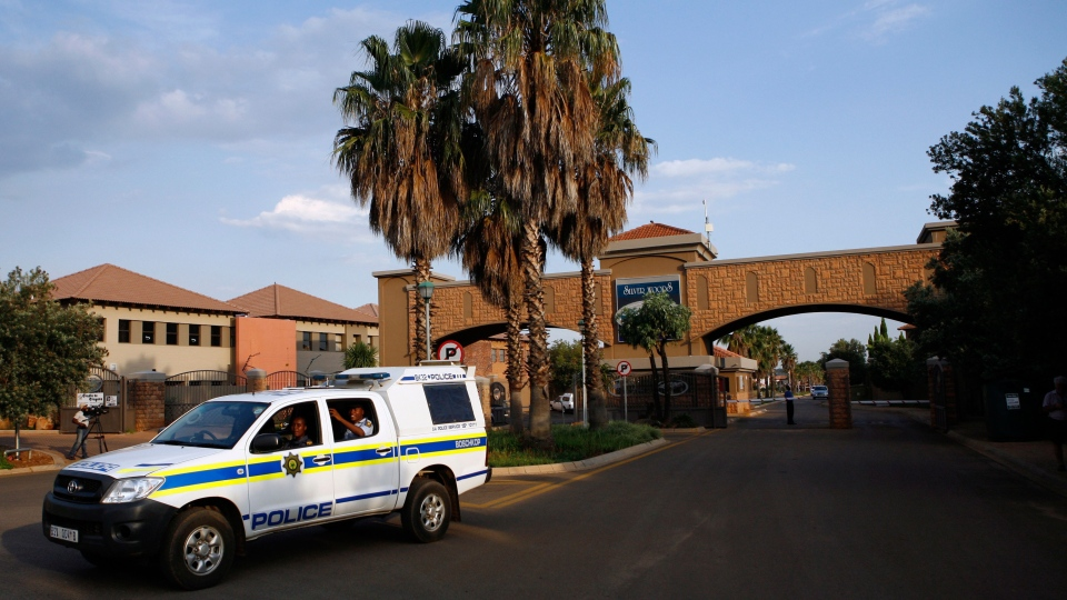A police vehicle leaves the housing estate where Olympian Oscar Pistorius lives in Pretoria, South Africa, Thursday, Feb. 14, 2013. (AP / Themba Hadebe)
