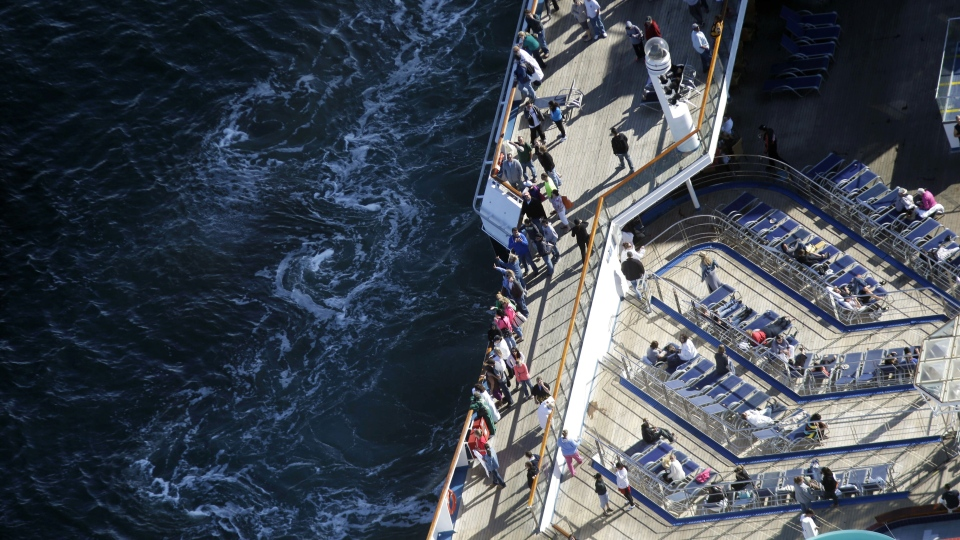 Passengers stand on the upper deck of the disabled Carnival Lines cruise ship Triumph as it is towed to harbor off Mobile Bay, Ala., Thursday, Feb. 14, 2013. (AP / Gerald Herbert)