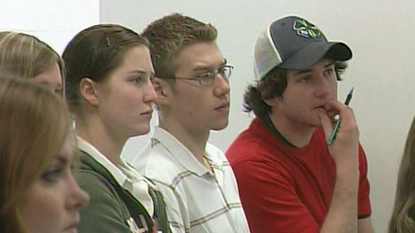 Students are seen in a classroom listening to a teacher.