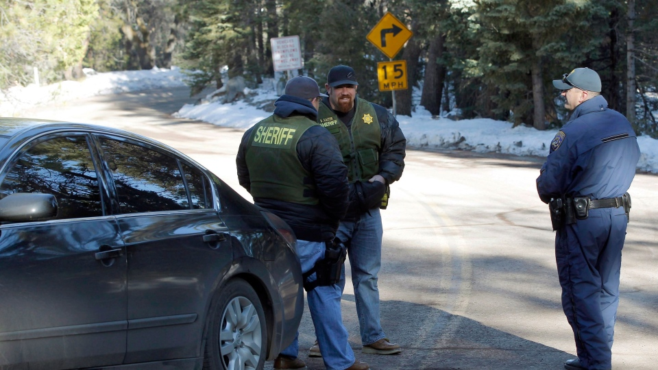 San Bernardino County Sheriff deputies man a roadblock near the site of a burned-out cabin where fugitive Christopher Dorner is thought to have burned to death near Big Bear, Calif.,  Thursday Feb. 14, 2013. (AP / Nick Ut)
