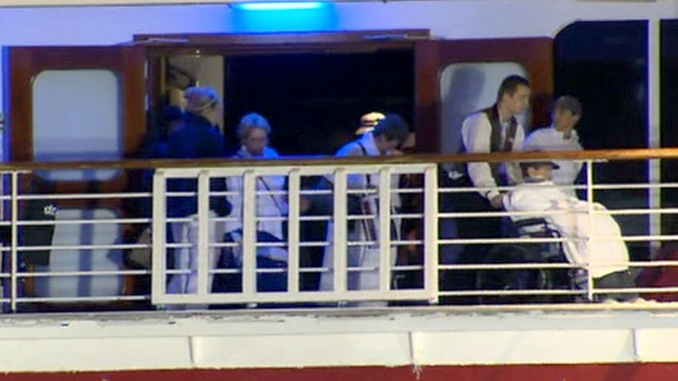 Passengers are assisted off of the Carnival Triumph in Mobile, Alabama.