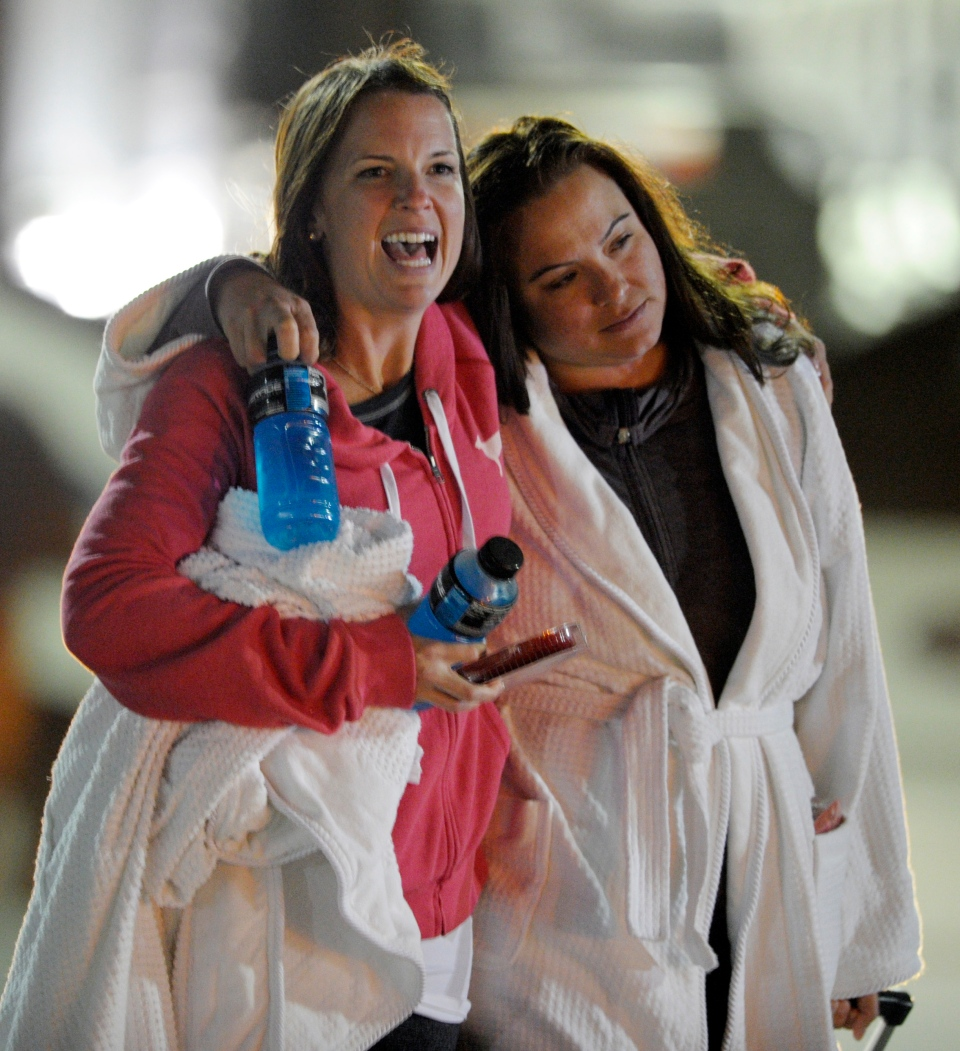 Kristina Courson, left, of Paris, Texas, is embraced by Jamie Hilliard, of Denison, Texas, after getting off the cruise ship Carnival Triumph in Mobile, Ala., Thursday, Feb. 14, 2013. (AP / G M Andrews)