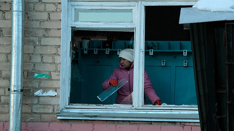 A woman cleans away glass debris from a window after a meteorite explosion over Chelyabinsk region on Friday, Feb. 15, 2013. (Yevgenia Yemelyanova, Chelyabinsk.ru)
