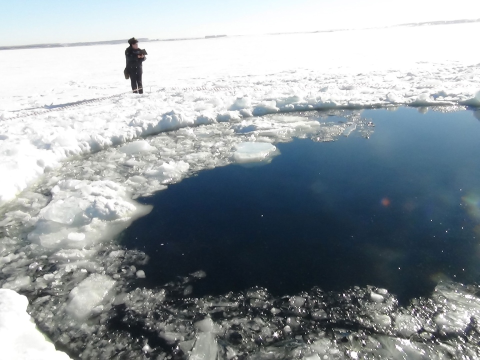 A circular hole caused by a meteor can be seen in the ice of Chebarkul Lake near Chelyabinsk, Russia, Friday, Feb. 15, 2013. (AP)