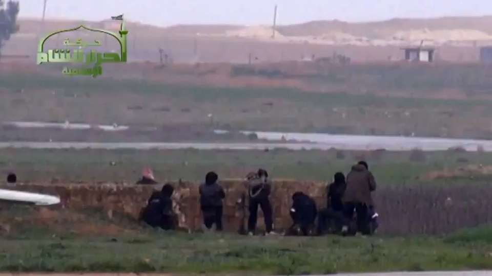 This image taken from video obtained from Ugarit News, which has been authenticated based on its contents and other AP reporting, shows Syrian rebels at Jarrah airfield in Aleppo province, Tuesday, Feb. 12, 2013. (Ugarit News via AP video)