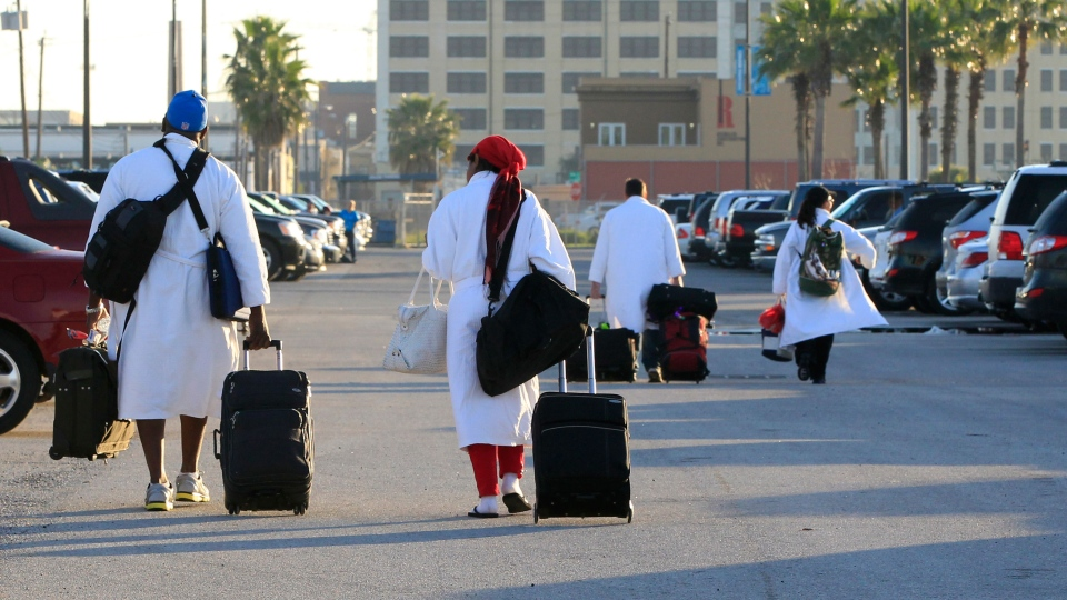 Passengers from the Carnival ship Triumph, all wearing their Carnival bathrobes, head to their cars after arriving in Galveston, Texas from Mobile, Ala. on Friday Feb. 15, 2013. (The Galveston County Daily News, Jennifer Reynolds)