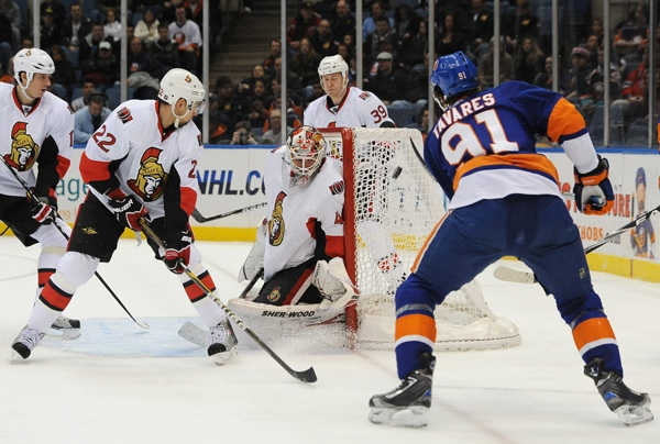 Ottawa Senators goalie Robin Lehner (40) of Sweden blocks a shot on goal by New York Islanders' John Tavares as Ottawa Senators' Chris Kelly (22) and Matt Carkner (39) defend from behind during the first period of an NHL hockey game Thursday, Jan. 13, 2011, in Uniondale, N.Y. (AP Photo/Kathy Kmonicek)