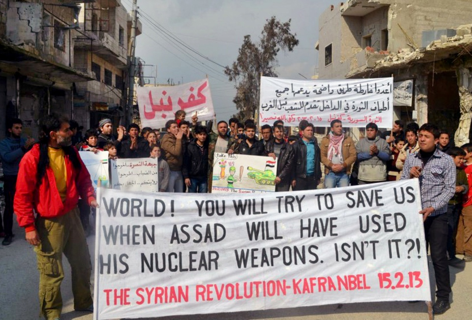 Anti-Syrian regime protesters carry banners during a demonstration, at Kafr Nabil town, in Idlib province, northern Syria, Friday, Feb. 15, 2013. (Edlib News Network ENN)