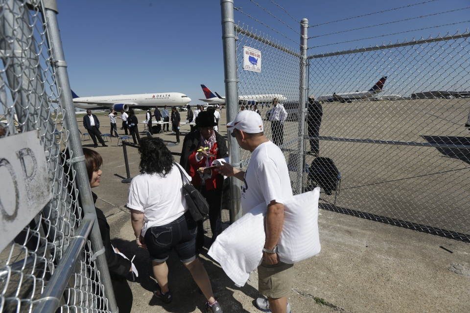 Passengers from the disabled Carnival Lines cruise ship Triumph board charter planes to return home, at Louis Armstrong International Airport in Kenner, La., Friday, Feb. 15, 2013. (AP / Gerald Herbert)