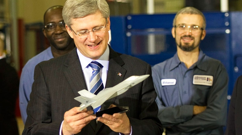 Prime Minister Stephen Harper looks at a model of a plane during a visit to the Heroux-Devtek plant on Friday, Jan. 14, 2011 in Mirabel, Que. The company announced Tuesday it is selling one-third of its business to an American company for $300 million in cash. (Ryan Remiorz / THE CANADIAN PRESS)