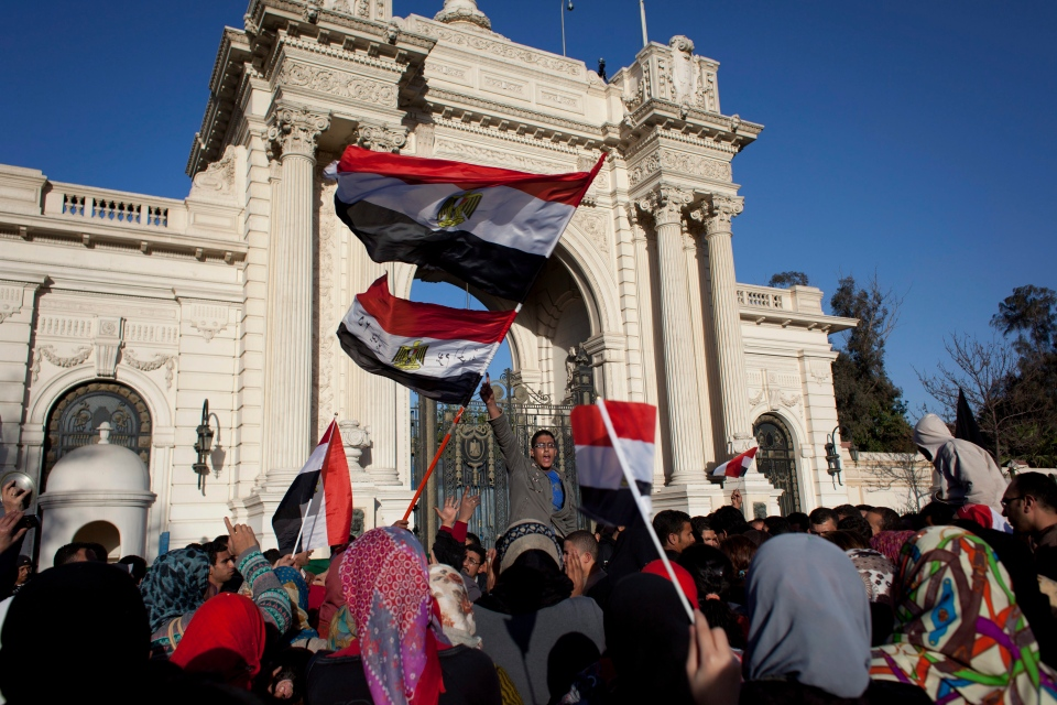Egyptian activists chant slogans and fly their national flag during an anti-president Mohammed Morsi protest in front of the entrance of the Qasr al-Kobba palace, one of the president's secondary palaces, in Cairo, Egypt, Friday, Feb. 15, 2013. (AP / Nasser Nasser)