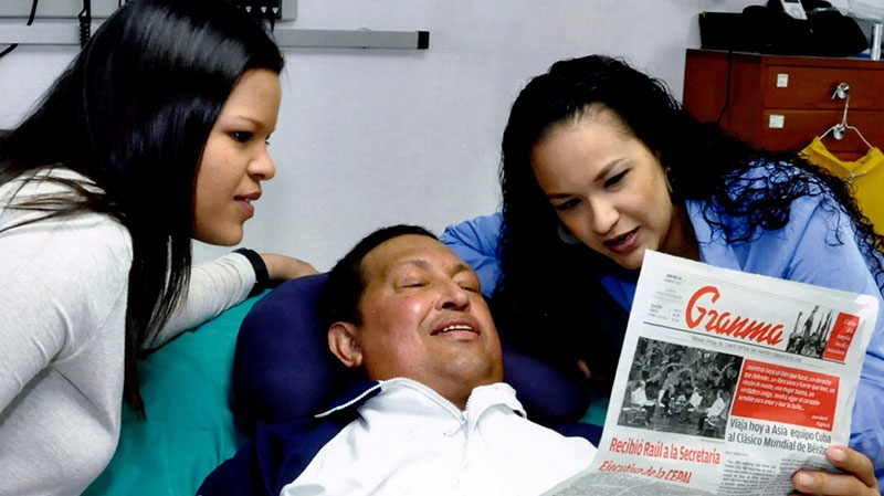 Venezuela's President Hugo Chavez, center, poses for a photo with his daughters, Maria Gabriela, left, and Rosa Virginia as he holds a copy of Cuba's state newspaper Granma at an unknown location in Havana, Cuba, Thursday, Feb. 14, 2013. (Miraflores Presidential Press Office)