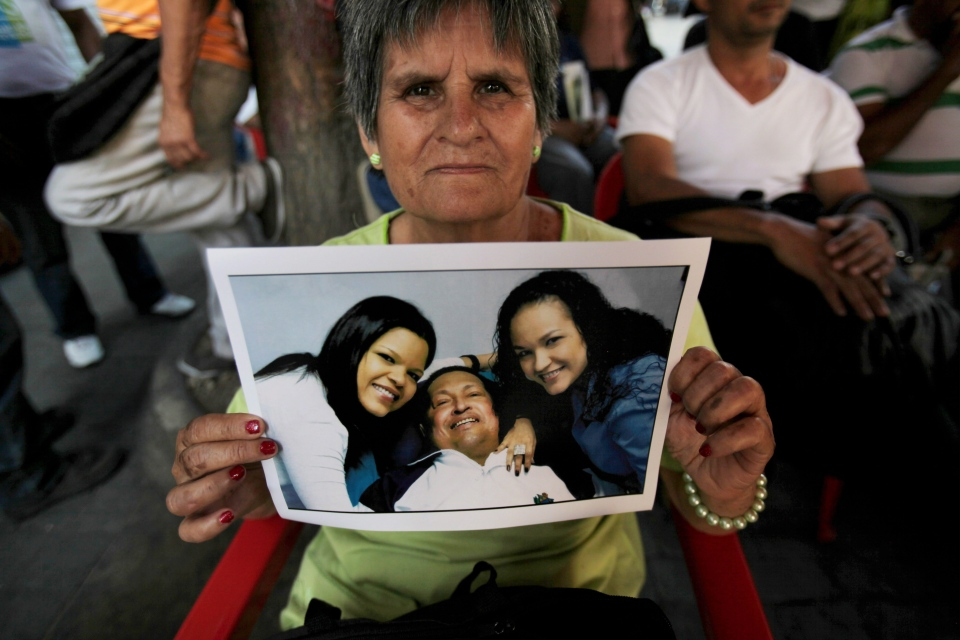 Carmen Rondon poses with a photo of Venezuela's President Hugo Chavez with his daughters Maria Gabriela, left, and Rosa Virginia, in Bolivar square where a vendor is selling the pictures in Caracas, Venezuela, Friday, Feb. 15, 2013. (AP Photo/Fernando Llano)