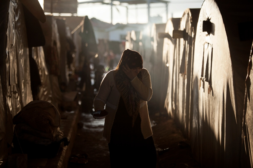 A Syrian refugee woman is seen between a line of tents in a refugee camp near Azaz, north of Aleppo province, Syria on Feb. 17, 2013. (AP / Manu Brabo)