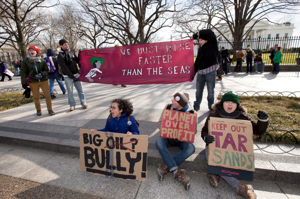 Katherine Saltzman, from front left to right, Daniel Leibovic, and Lola Katan Kourako, cheer protestors marching in front of the White House in Washington during a rally calling on President Barack Obama to reject the Keystone XL oil pipeline from Canada on Sunday, Feb. 17, 2013. (AP / Manuel Balce Ceneta)