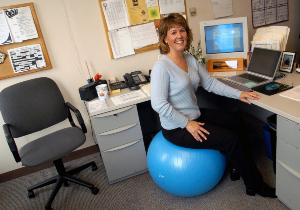 Pam O'Donnell, director of member service at the Boston-based International Health, Racquet & Sportsclub Association, sits at her desk on an inflatable exercise ball. (AP / Angela Rowlings)