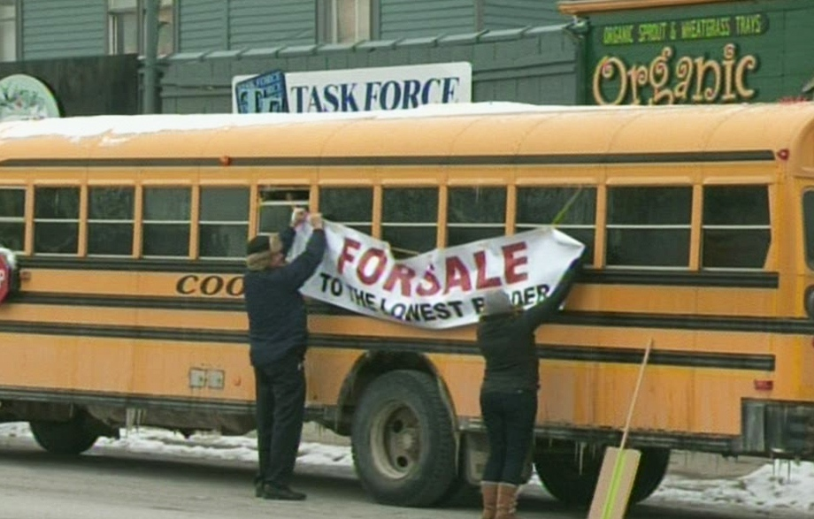 Protestors hang a 'For Sale' sign on a school bus in Guelph, Ont., on Monday, Feb. 18, 2013. (CTV Kitchener)