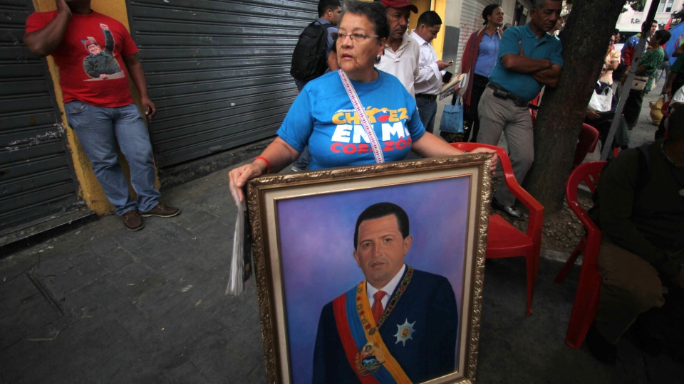 A woman holds a painting of President Hugo Chavez as supporters gather around Bolivar square after his return to the country in Caracas, Venezuela, Monday, Feb. 18, 2013. (AP / Fernando Llano)
