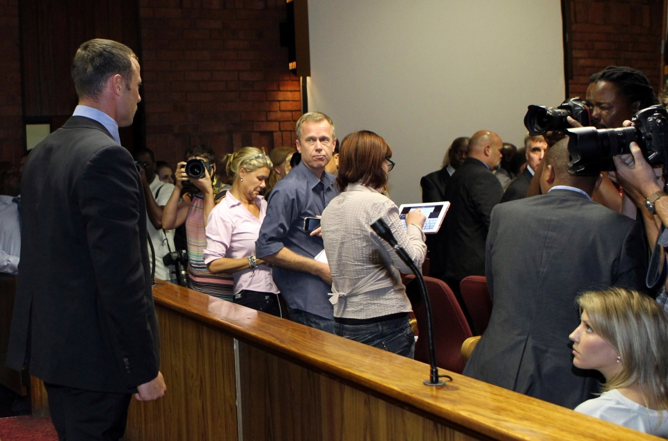 Olympic athlete Oscar Pistorius, left, stands as the judges leaves the court, during his bail application at the magistrate court, in Pretoria, South Africa, Tuesday, Feb. 19, 2013. (AP/Themba Hadebe)
