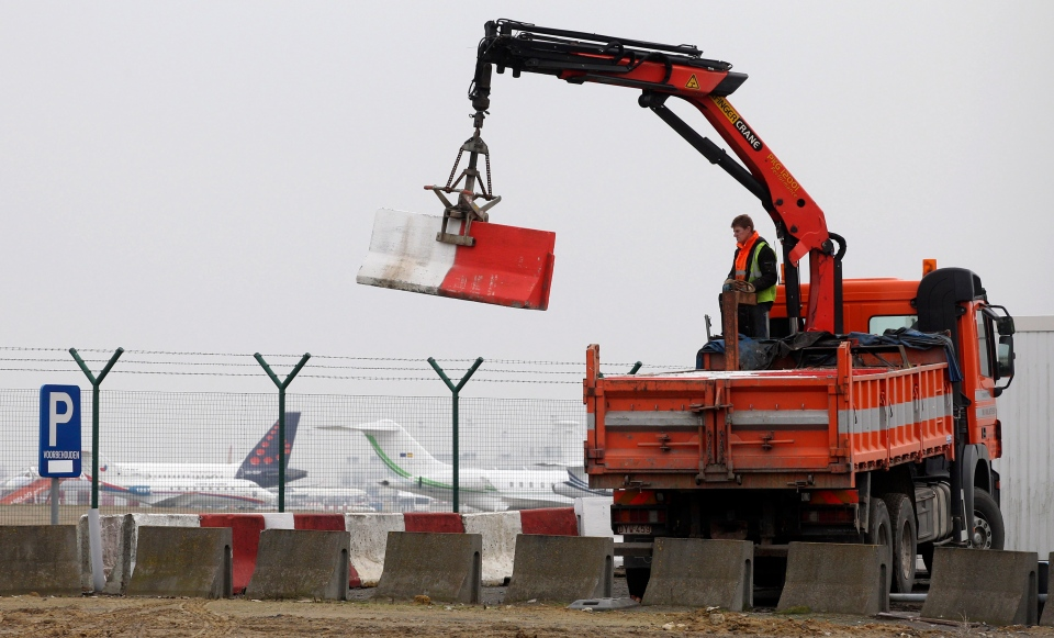 Workers place concrete blocks to block access to a security fence next to the tarmac, at Brussels international airport on Tuesday, Feb. 19, 2013.  (AP / Yves Logghe)