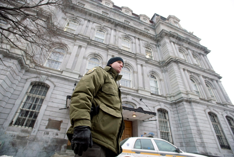 A Surete du Quebec officer stands outside City Hall in Montreal on Feb. 19, 2013, during a raid. (Graham Hughes/THE CANADIAN PRESS)
