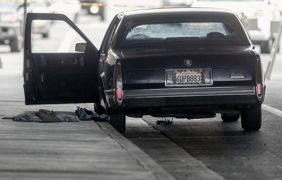 A vehicle riddle with bullet holes is part of a crime scene on Red Hills Ave. in Tustin, Calif.,  on Feb. 19, 2013. Police say a chaotic 25-minute shooting spree through Orange County left a trail of dead and injured victims before the shooter killed himself. (AP Photo/Damian Dovarganes)
