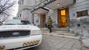 A Sûreté du Québec officer walks from City Hall during a raid by UPAC on the premises in Montreal on Tuesday, Februray 19, 2013. (Graham Hughes / THE CANADIAN PRESS)