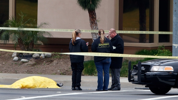 Investigators stand next to a tarp covered body in Orange, Calif., Tuesday, Feb. 19, 2013. (AP/Jae C. Hong)