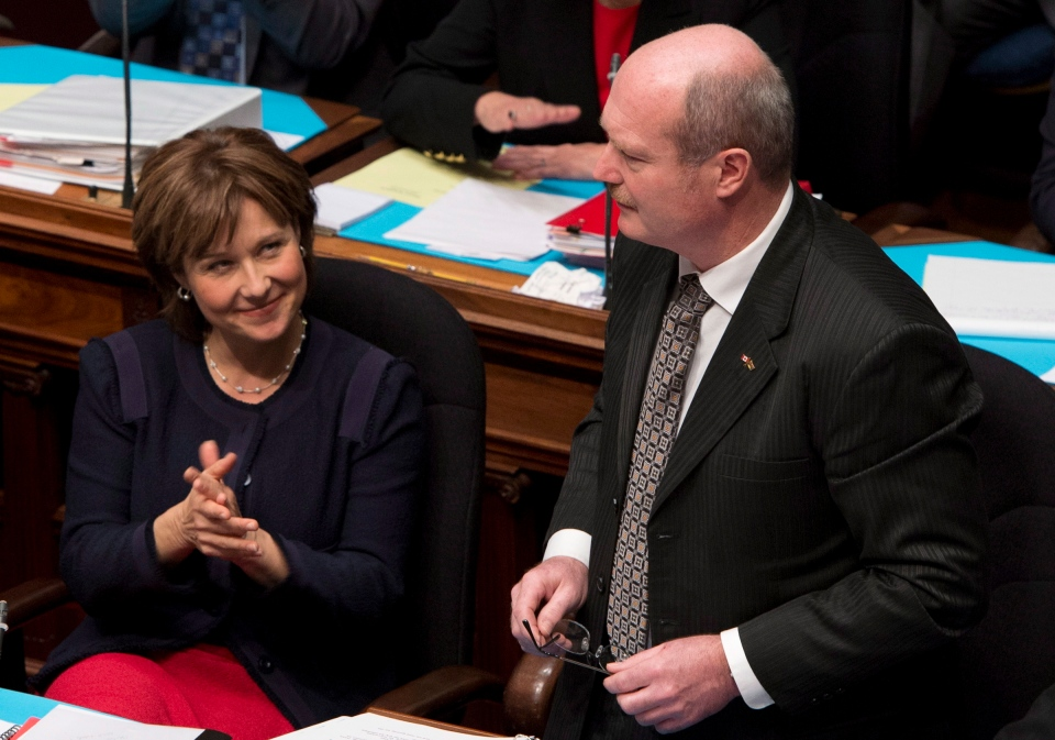 Premier Christy Clark, left, looks on as British Columbia Finance Minister Mike de Jong tables the budget in the B.C. Legislature in Victoria, Tuesday, Feb. 19, 2013. (Jonathan Hayward/THE CANADIAN PRESS)