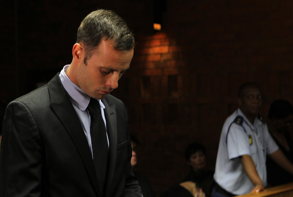 Olympic athlete Oscar Pistorius stands inside the court as a police officer looks on during his bail hearing at the magistrate court in Pretoria, South Africa, Wednesday, Feb. 20, 2013. (AP / Themba Hadebe)