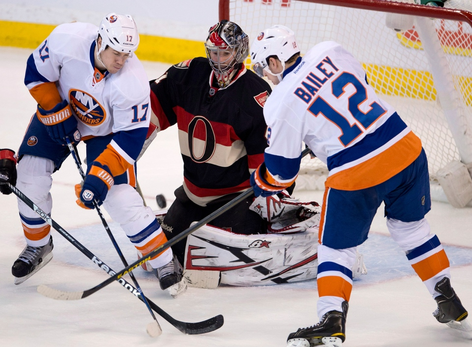 New York Islanders center Josh Bailey(right) and Matt Martin(left) try to put the puck past Ottawa Senators goalie Craig Anderson during third period NHL action in Ottawa on Tuesday February 19, 2013. Anderson stopped 37 shots as the Senators defeated the Islanders 3-1. THE CANADIAN PRESS/Adrian Wyld